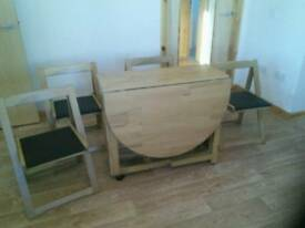 Oak effect folding table with four chairs.