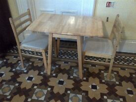 practically new hardwood folding dining table with two upholstered chairs