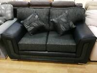 Stunning black fabric and faux leather 2 seater sofa with leaf cushion design