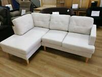 Cream fabric corner sofa with chaise and large wooden legs