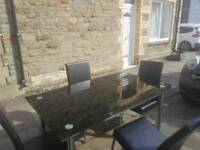 Black glass table and 4 chairs. Free local delivery