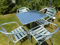 set of four silver chairs and silver table