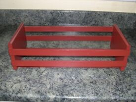 A wooden plant pot holder in a deep red colour.