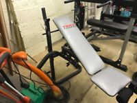 York 500 incline weight bench with variety of weights and bars.