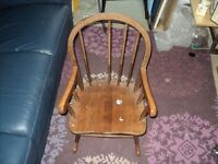 a very old rocking chair suitable for a child. there is a spindle missing.