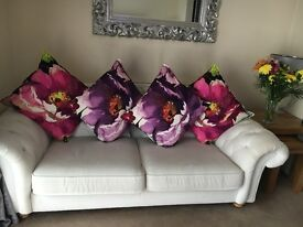 Cream sofa with matching purple accent chair and cushions