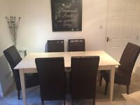 Dining table with 6 brown leather chairs and matching coffee table, in good condition.