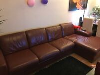 Brown leather sofa with footrest and pillows