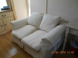 Cream 2 seater sofa with loose covers and additionl loose covers never used. Finchley, north London