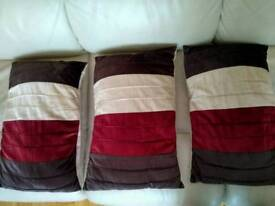 Three decorative red pillows