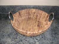 A rush fruit basket with stainless steel handles.