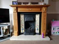 Cast iron gas fire and pine surround.