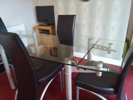 Extending glass top dining table with 6 black faux leather chairs