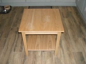 A square four legged wooden table.