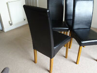 Set of four wooden and faux black leather in very good condition