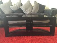 Black glass TV stand with 2 shelves.