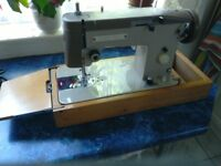 Electric Sewing Machine. Works okay but slight damage to wooden fold out tray. See photos.