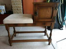 Solid wood, mahogany coloured phone/console table, with cream padded seat and storage cupboard.