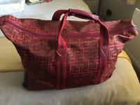 Red and brown patterned small trolly suitcase