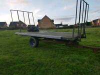Tractor tipping bale trailer with front and rear bale holders