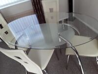A glass dinning table and 4 chairs