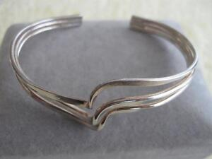 A DECORATIVE & UNIQUE-STYLED SILVERTONE CUFF-STYLED BRACELET