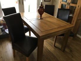 Table and four brown leather chairs excellent condition .Can be extended to seat 8 people