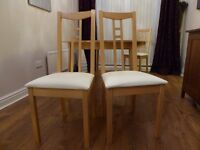Beech Ikea extending table and 4 chairs. Round to oval table. Chairs have cream fabric seat covers.
