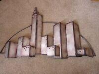 A large piece of metal wall art from Dunelm, cityscape style, good wall filler, used VGC.