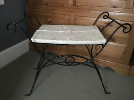 Wrought iron effect metal stool with cushion.