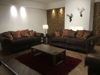 3 sofas 2 three seated and one two seated excellent condition in brown leather with print cushions.
