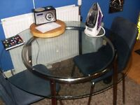 round glass table and 4 blue chairs