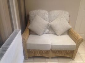 Beautifully presented 2 seater cane coservatory sofa in immaculate condition . Foot stool to match