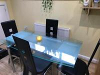 Extendable glass dining table and leather chairs
