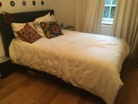 Black double bed with storage space for sale