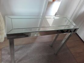 Console table in mirrored glass panelling.