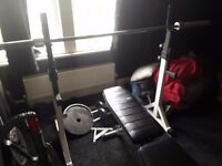 OLYMPIC WEIGHT AND BENCH SET. Large selection of weights. Bench adjusts to various positions.