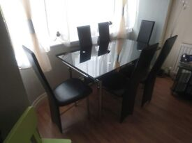 Black glass dining table plus six chairs
