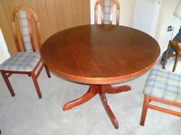 Round extending wooden table and four upholstered chairs