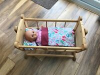 A Dolls wooden swing crib with matching bedding plus doll