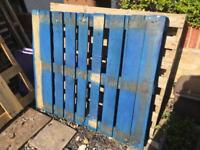 Multiple wooden pallets and a crate