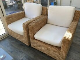 Two stylish, modern woven rattan chairs.