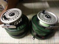 pair of fly reels in cases
