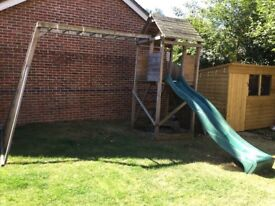 Wooden climbing frame with a slide.