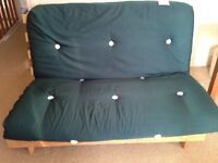 Double futon sofa bed with wooden frame and dark green cushion in excellent condition