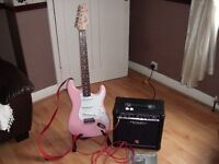 Squier by Fender stratocaster electric guitar in pink with strap