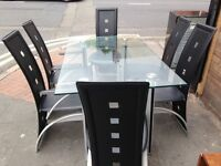 A glass dinning table with leather chairs for sale