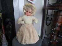 A VINTAGE MUSICAL DOLL NIGHTDRESS HOLDER. 15 INCHES TALL APPROX.