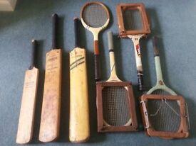 Three antique cricket bats and four antique tennis rackets
