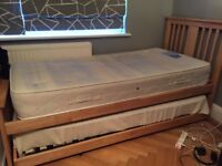 Single wooden bed. Roll out spare bed underneath with foldaway legs. Slatted bases. 2 mattresses.